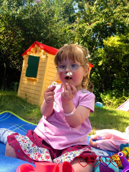 Two year old Jessica sitting in the garden holding a daisy