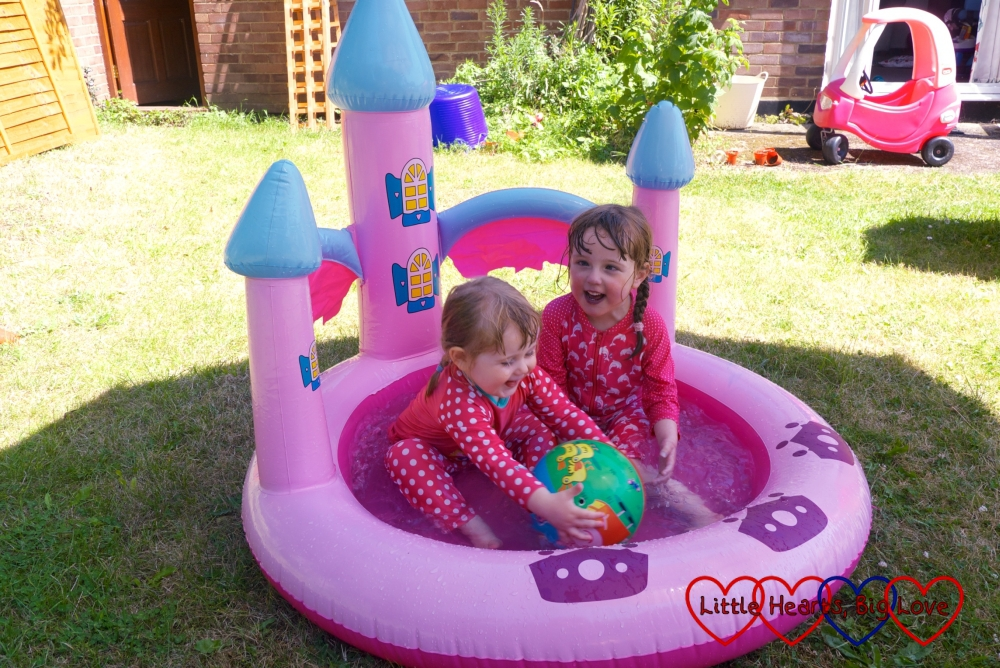Jessica and Sophie splashing about with a ball in the paddling pool