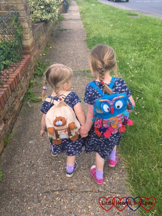 Sophie and Jessica walking along hand-in-hand with Sophie wearing a teddy bear backpack and Jessica wearing an owl backpack
