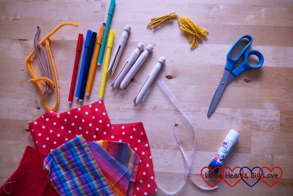 Scraps of fabric, marker pens, pipe cleaners, clothes pegs, pieces of wool, scissors, glue and ribbons