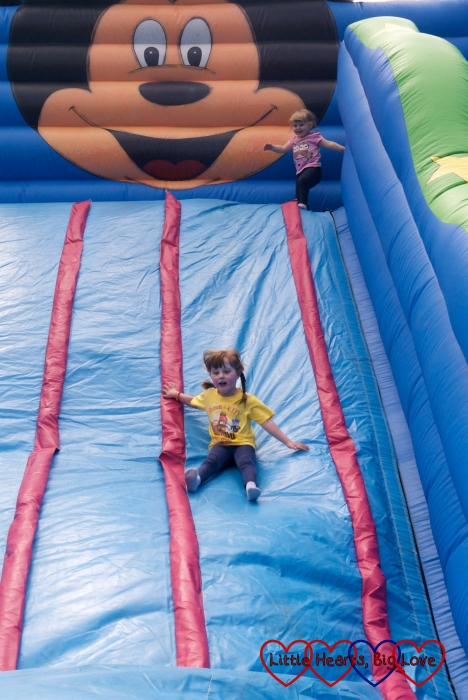 Jessica sliding down the giant inflatable slide with Sophie at the top