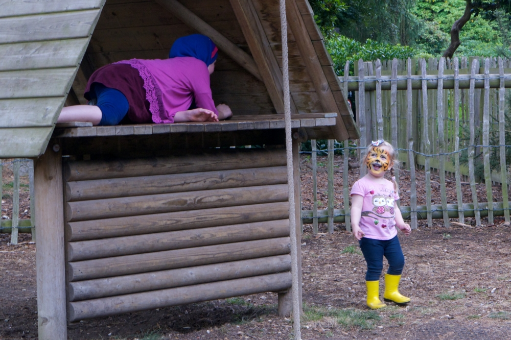 A tiger-faced Sophie prowling around the huts in the playgruond while an older girl hides from her
