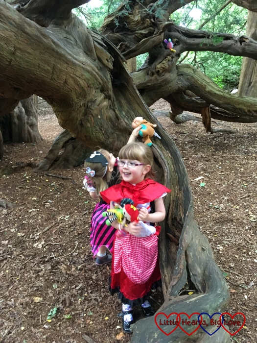 """Jessica in her Little Red Riding Hood costume in the foreground with Sophie in her pirate costume putting toys down the """"slide"""" in the yew tree in the background"""