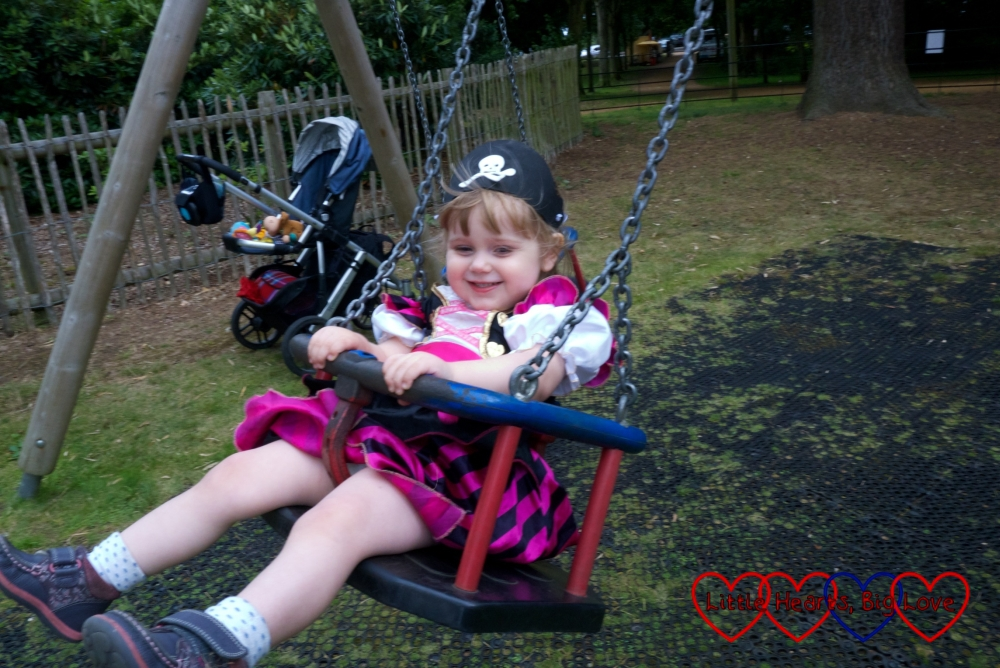 Sophie in her pirate outfit swinging on the toddler swing
