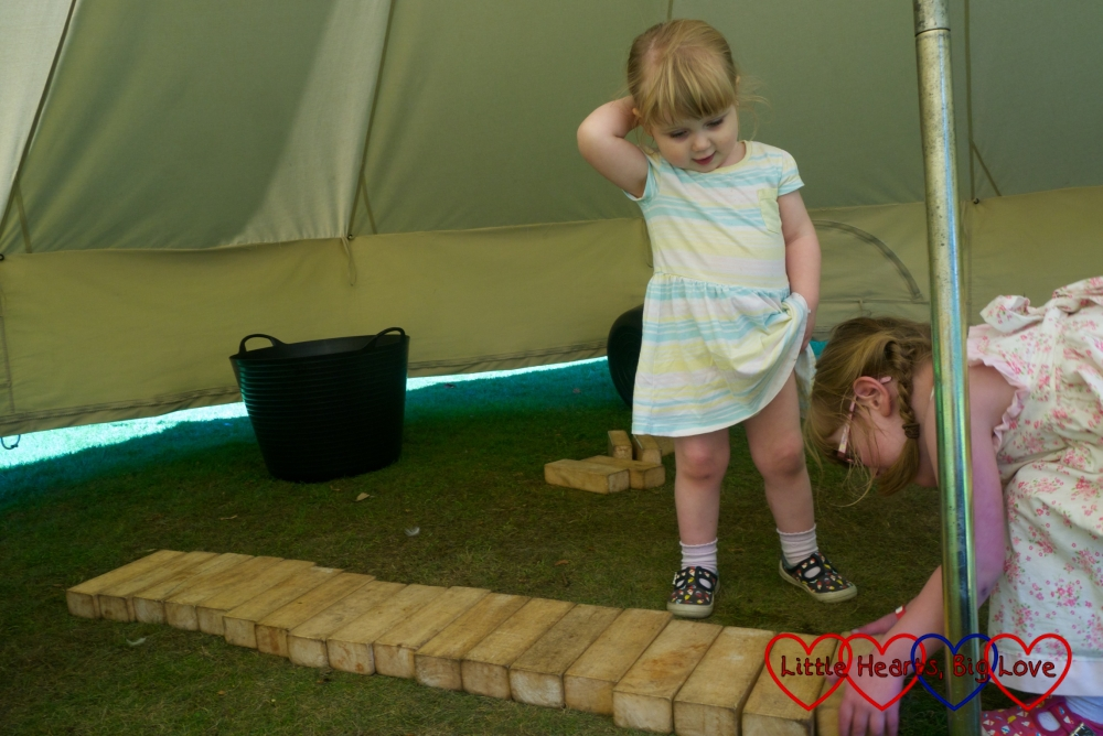 Sophie making a xylophone with the wooden blocks