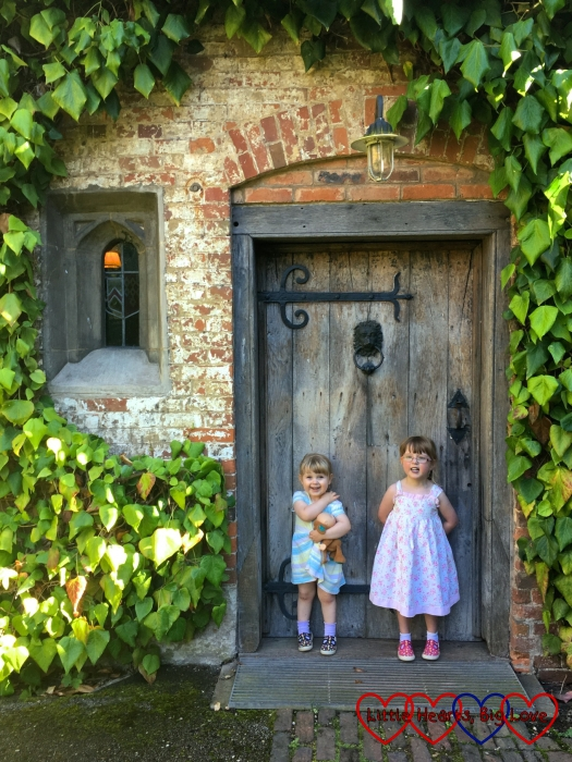 Sophie and Jessica in front of a door in the inner courtyard at Baddesley Clinton