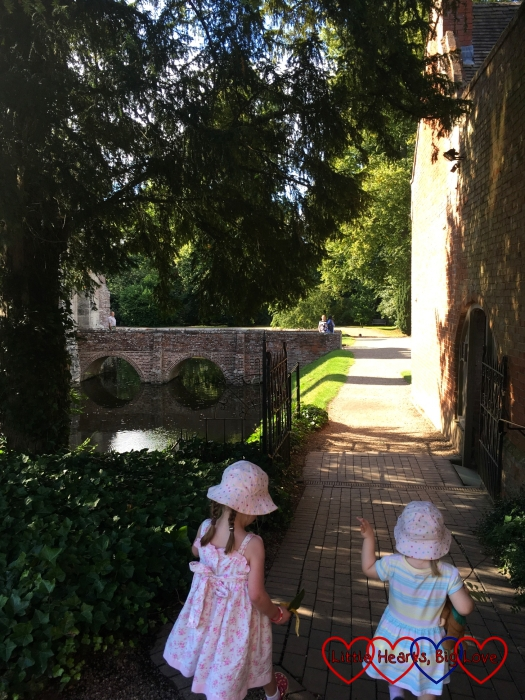 Jessica and Sophie walking towards the bridge and the house at Baddesley Clinton
