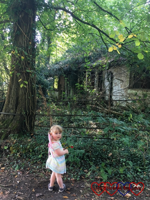 Sophie standing outside a disused house in the woods