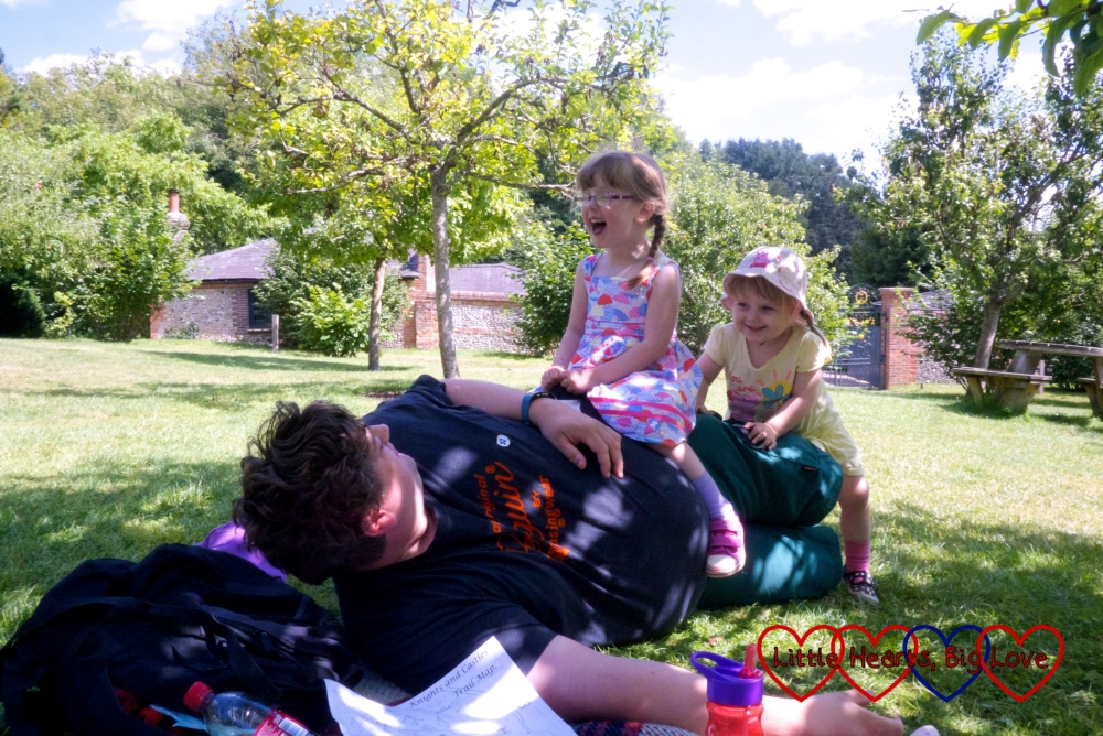 Hubby lying in the sunshine with the girls sitting on him