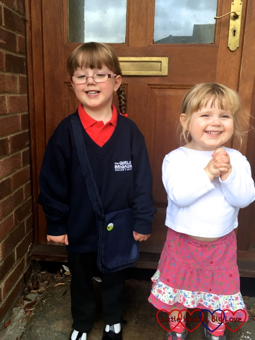 Jessica in her Girls' Brigade uniform and Sophie in a white top and pink spotty skirt with her hands clasped together