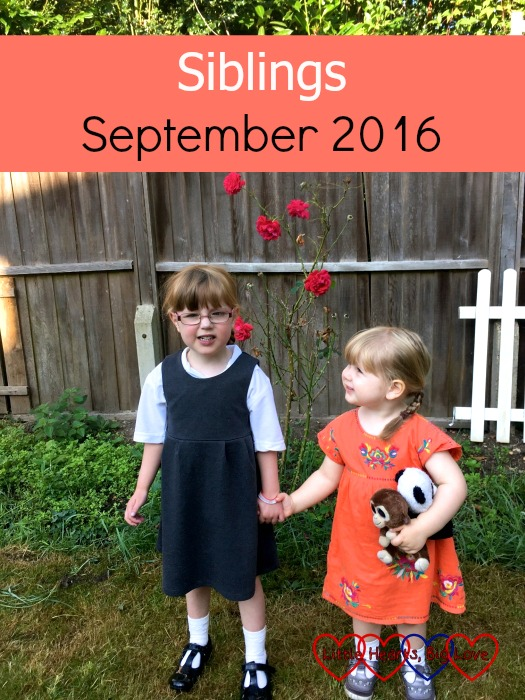 Jessica in her school uniform and Sophie in an orange dress holding hands in front of the roses in the garden - Siblings: September 2016