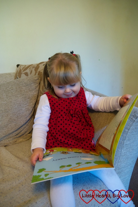 "Sophie sitting on the sofa ""reading"" the Harty Hedgehog and his BuZZy Friends book"