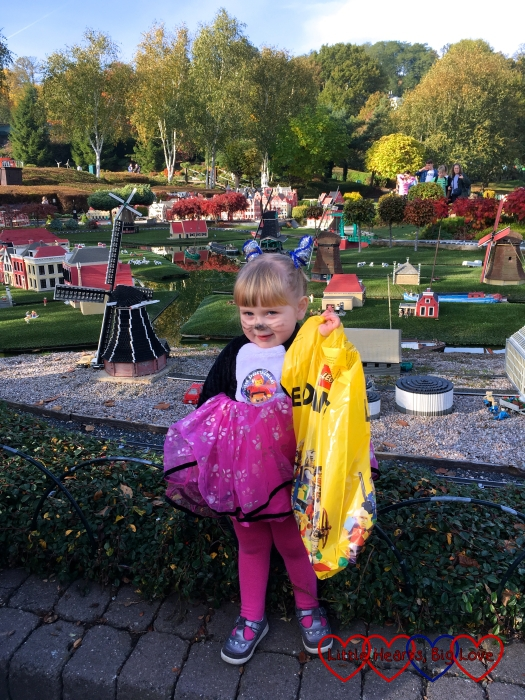 Sophie at Miniland wearing her cat costume and holding the bag containing her prize for winning the fancy dress competition