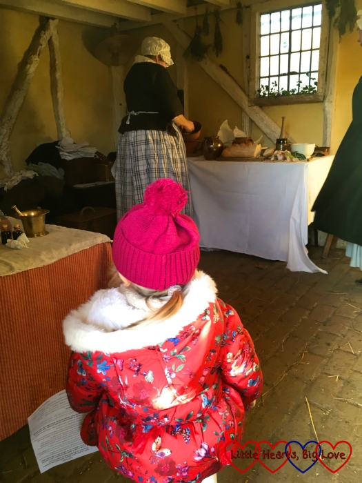 Sophie watching the women preparing a meal in Leagrove Cottage