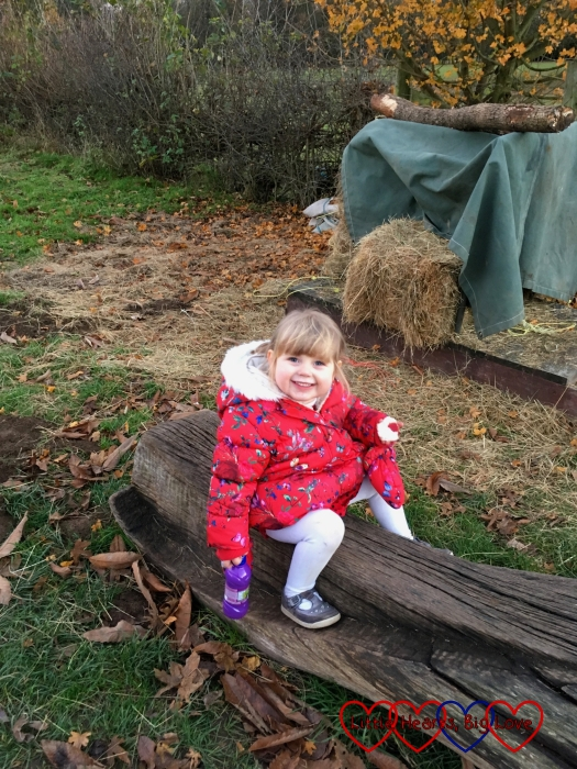 Sophie sitting on a bench with a big smile on her face