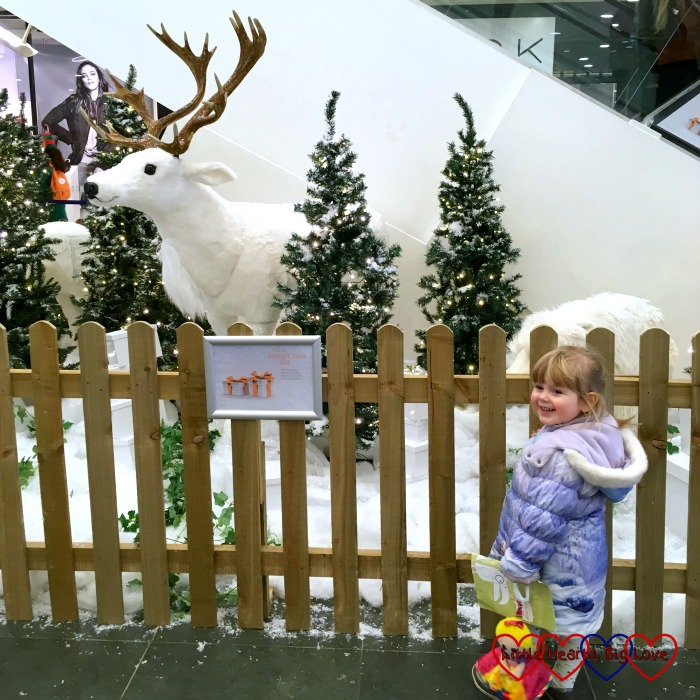 Sophie looking at the model of the reindeer and polar bear in the snow at the shopping centre