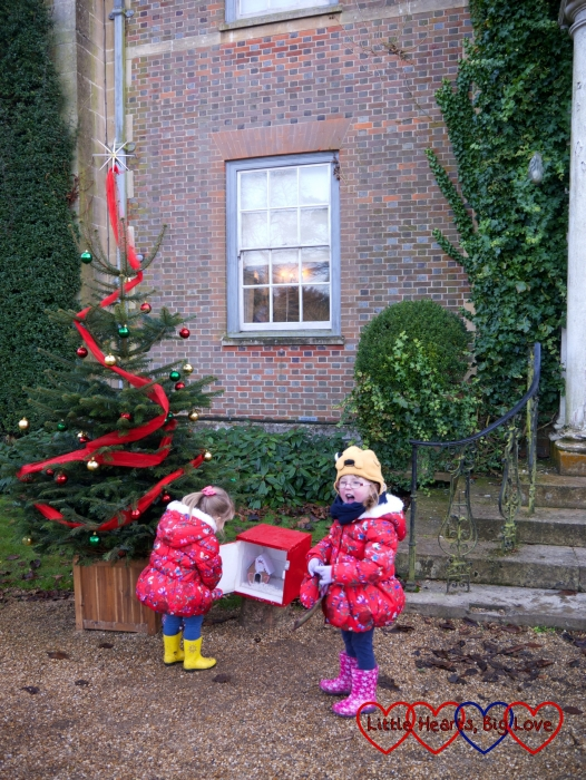 Jessica and Sophie opening one of the boxes near the house next to a decorated Christmas tree
