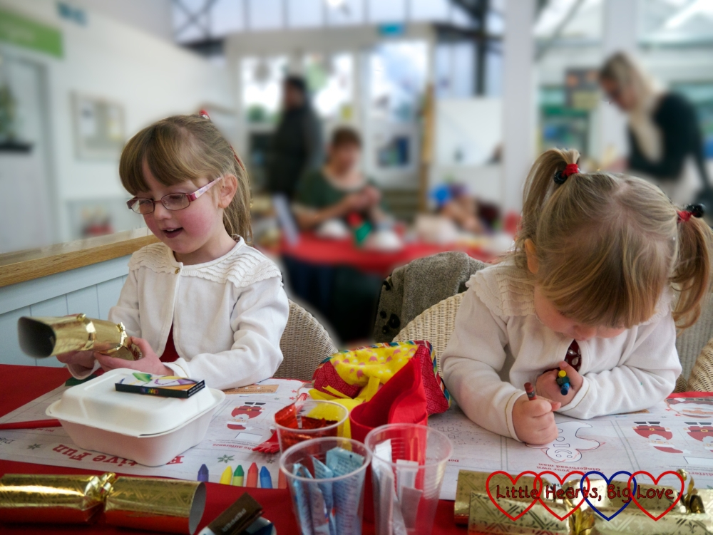 Jessica and Sophie looking at the crackers and activity sheets laid out on the tables ready for tea with Father Christmas