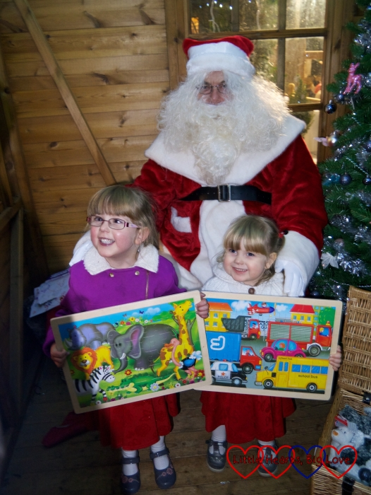 Jessica and Sophie with their wooden jigsaw puzzles posing for a photo with Father Christmas