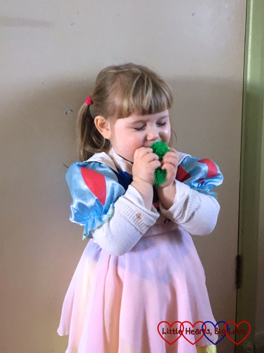 Sophie wearing her princess dress and kissing her toy frog