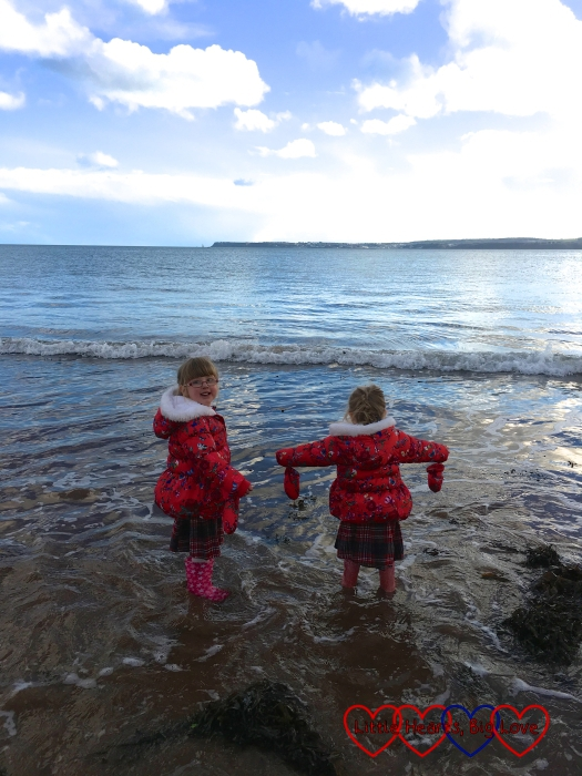 Jessica and Sophie paddling in the sea in their wellies