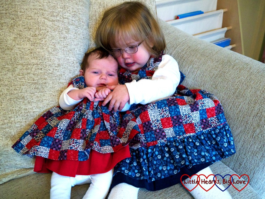 Baby Sophie and a 2-year old Jessica in co-ordinating patchwork print reversible dresses from Seesaw Children's Clothes