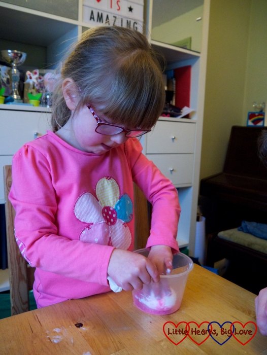 Jessica dipping the glue-covered egg into the glitter