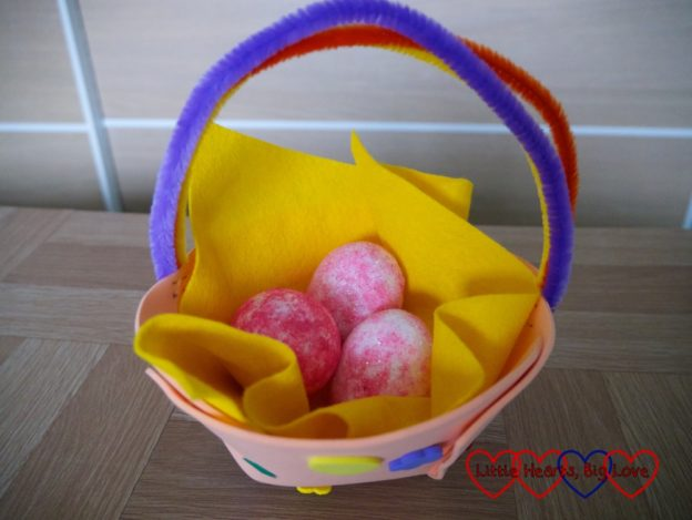 The finished Easter basket filled with pink glittery eggs