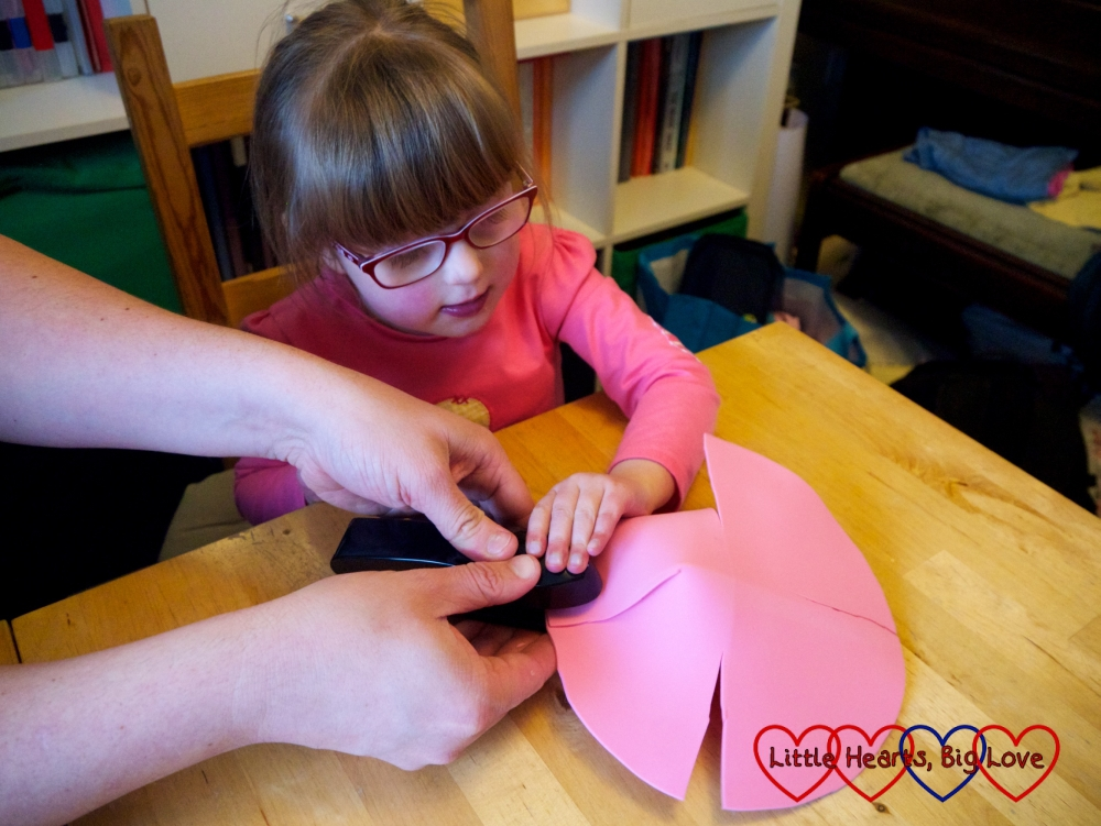 Daddy helping Jessica to fold up the sides of the foam craft circle and staple them to form a basket shape
