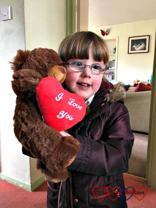 Jessica cuddling a teddy bear holding a big red heart - her bravery buddy