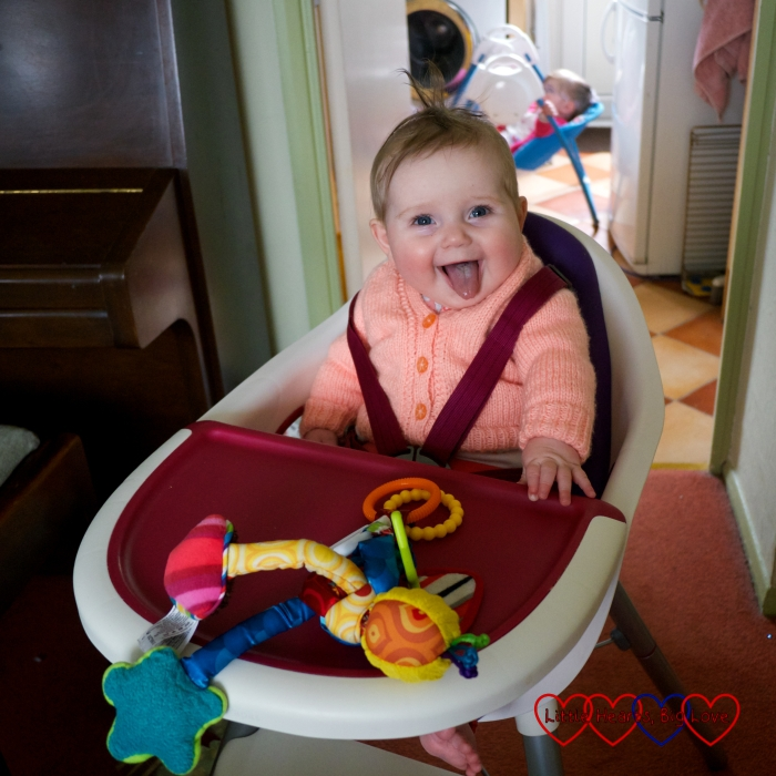 Sophie sitting in her high chair with a big grin on her face