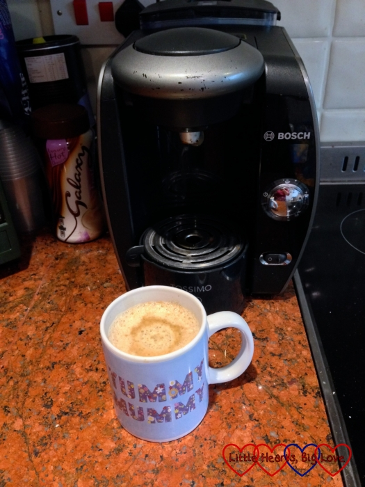 A cup of coffee in front of a Tassimo machine
