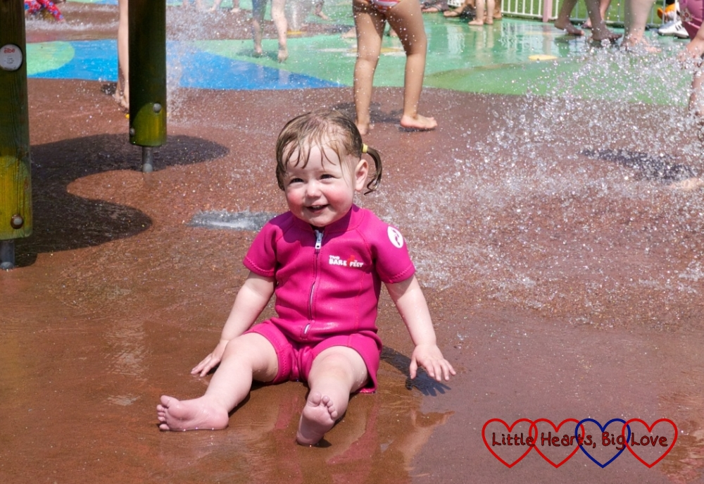 Jessica playing in the splash pool at Peppa Pig World wearing her wetsuit from Heartline