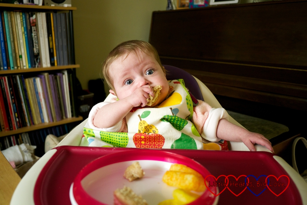 Jessica sitting in her high chair eating lunch