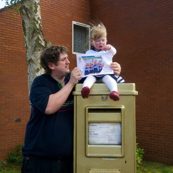 Jessica sitting on a gold postbox in Oxford with Daddy standing next to her