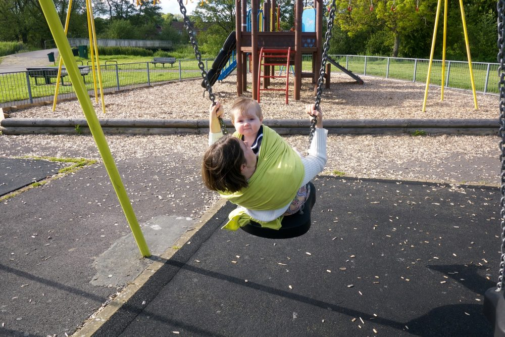 Sophie in the wrap on the swing with Mummy