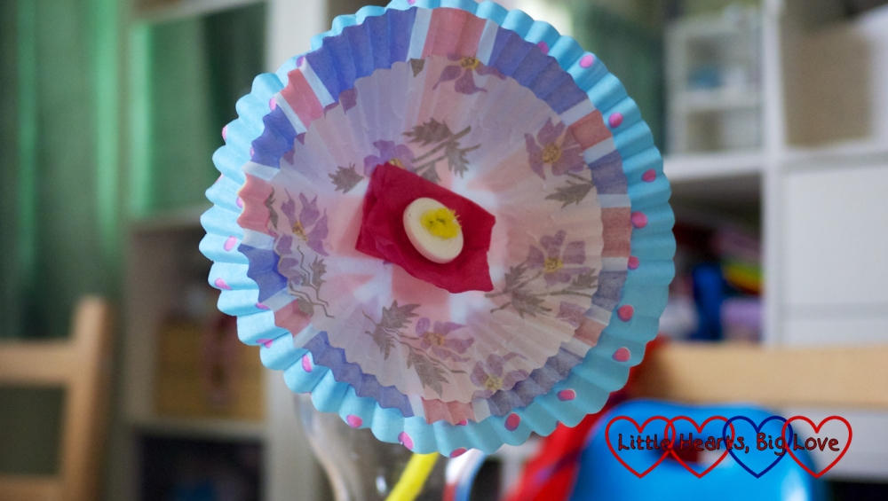 A flower made from three cupcake cases, tissue paper, pipe cleaner and a button