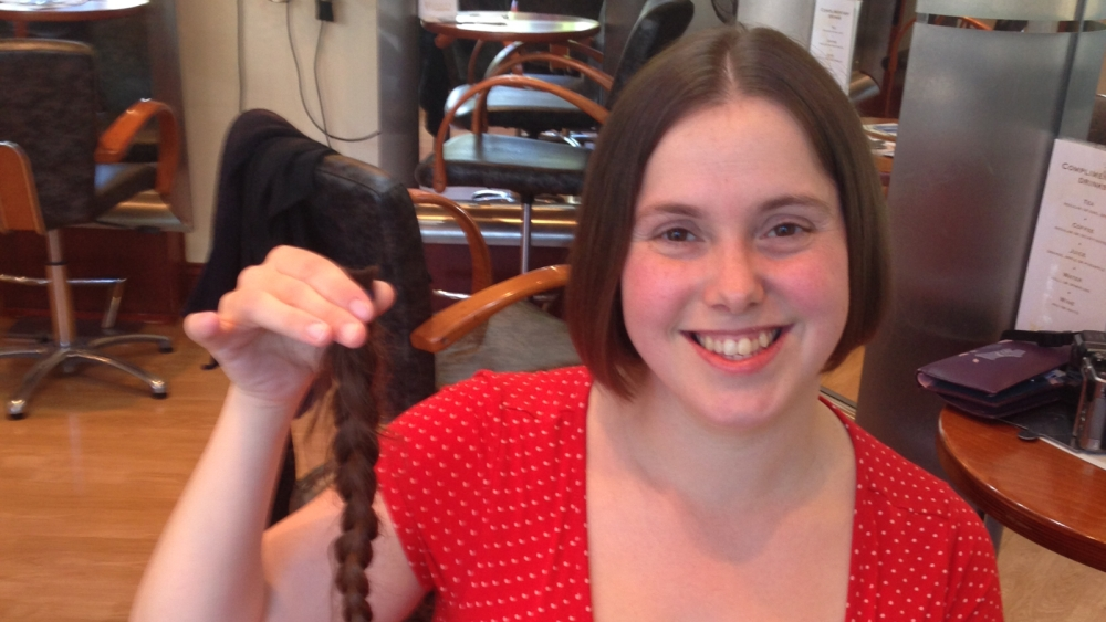 Me holding a plait of hair to donate to the Little Princess Trust