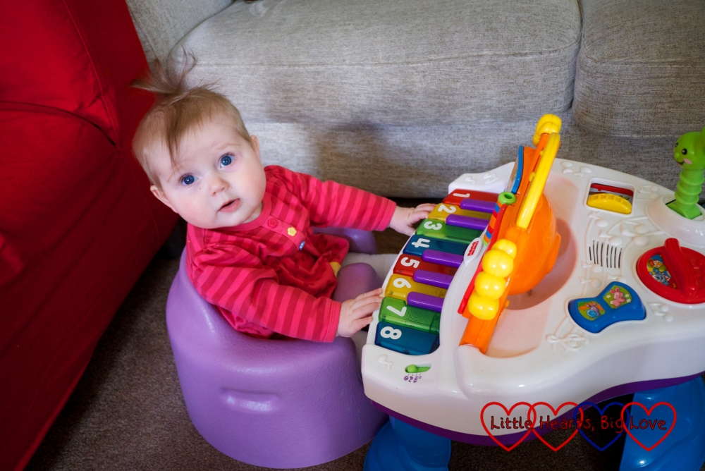 Sophie sitting in the Bumbo and playing her toy piano