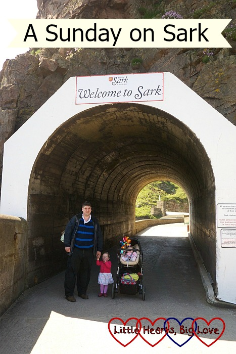 """Hubby, Jessica and Sophie (in her buggy) at the entrance to a tunnel with """"Welcome to Sark"""" above them"""