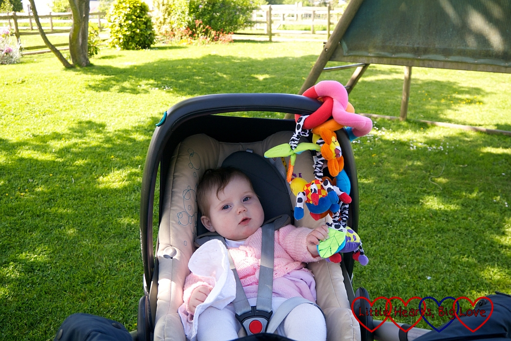 Sophie sitting in her buggy in the sunshine