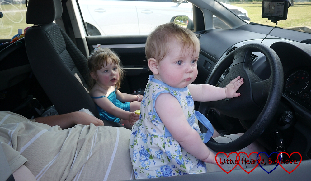 Jessica and Sophie sitting in the front of the car with Daddy