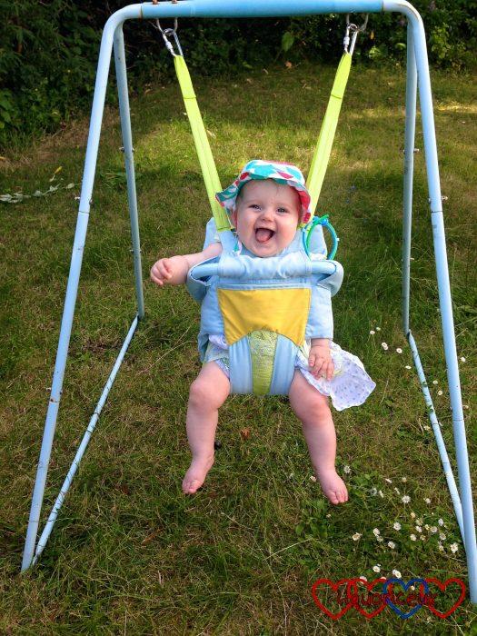 Sophie in her baby swing in the garden