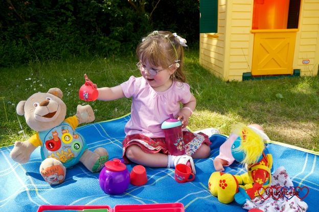 Jessica having a picnic with her toys in the garden