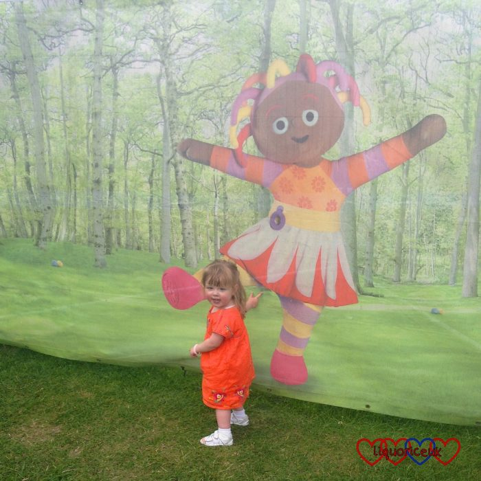 Jessica standing next to a picture of Upsy Daisy