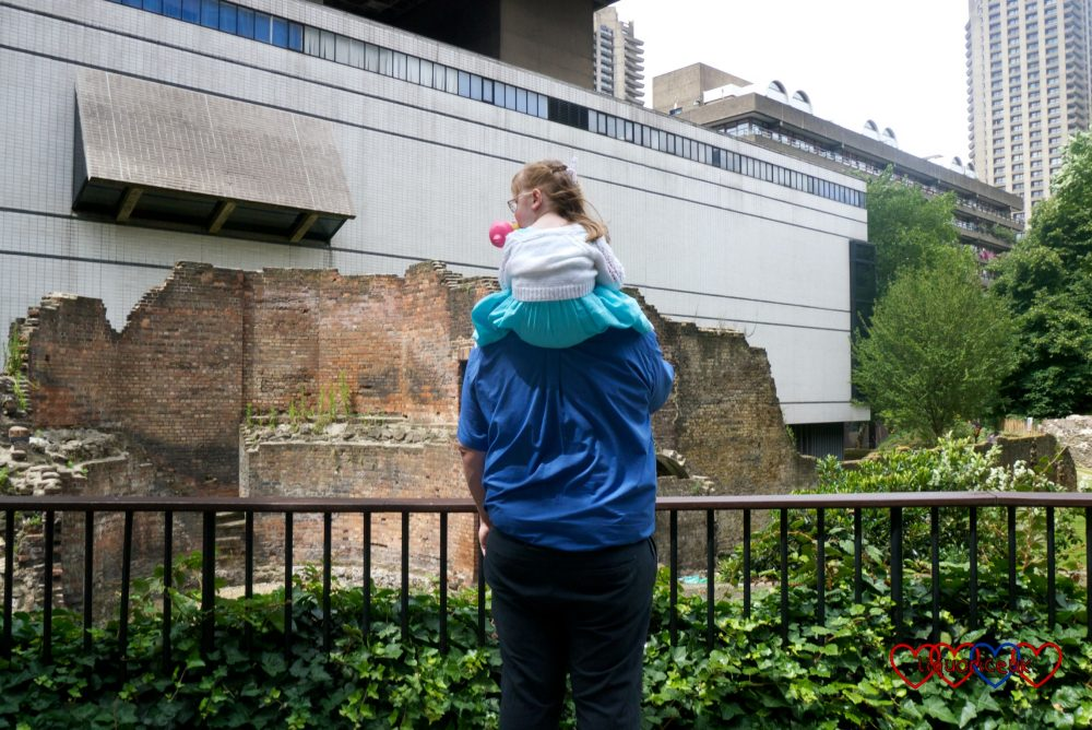 Jessica on hubby's shoulders looking at a section of the London Wall