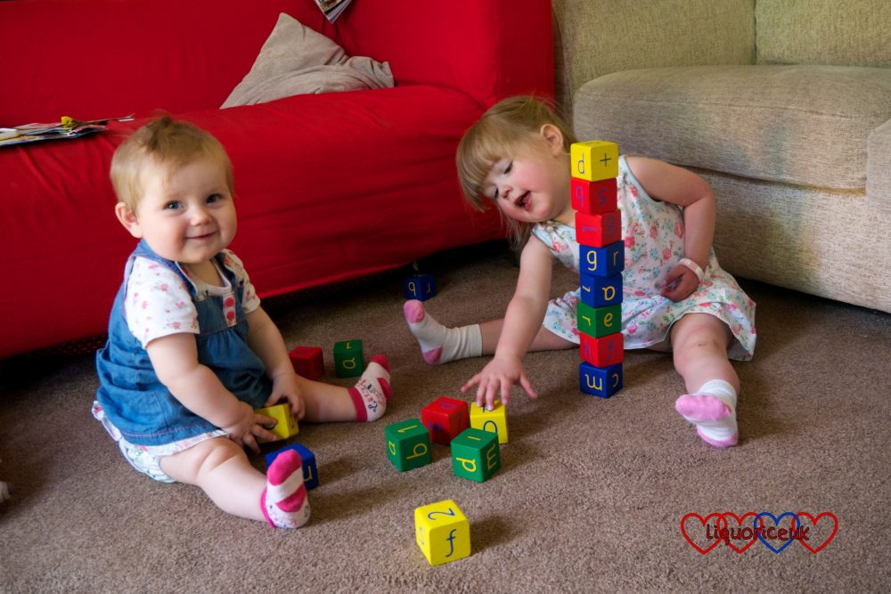 Jessica building a tower and Sophie looking cheeky