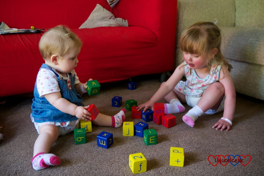 Jessica and Sophie sitting on the floor playing with coloured bricks