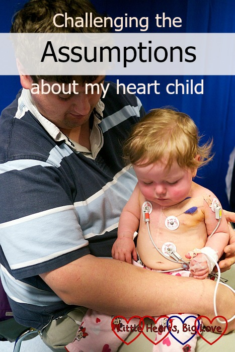 """Jessica sitting on Daddy's lap with her chest covered in ECG stickers and leads - """"Challenging the assumptions about my heart child"""""""