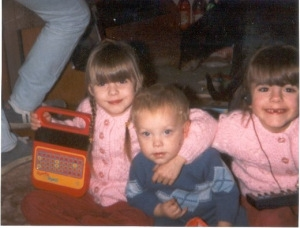 Me holding a Speak and Spell toy with my twin sister and nephew when we were small children